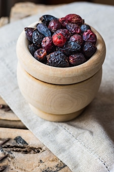 Dried rose hip berries in wood bowl, on linen towel, health concept