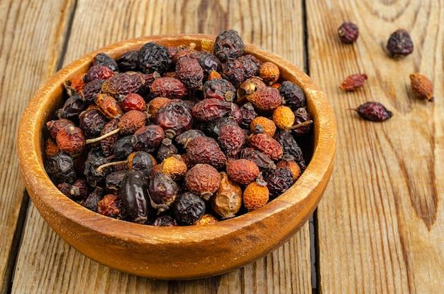 Сушеные плоды шиповника в деревянной миске как натуральный витамин с