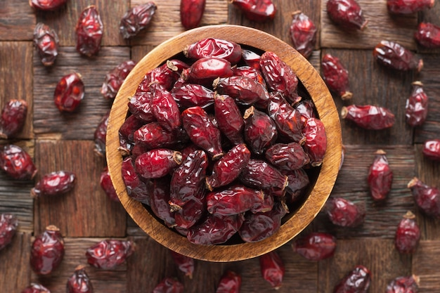 Сушеные ягоды шиповника или шиповника в деревянной миске, вид сверху.