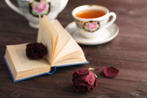 開いた本を置く乾燥したバラ