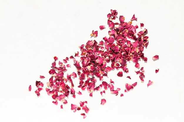 Сушеные лепестки роз на светлом фоне вид сверху пространство для текста