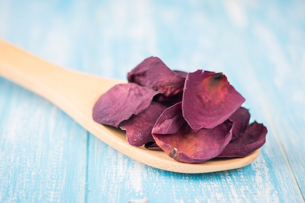 Dried rose petals in a wooden spoon on a rustic table.