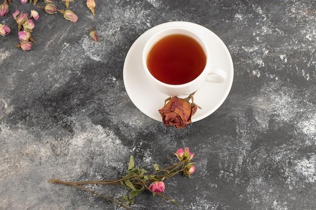 石のテーブルの上に置かれた熱いお茶のカップで乾燥したバラのつぼみ。