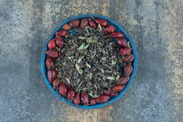 Сушеные плоды шиповника и чайные листья на синей тарелке.