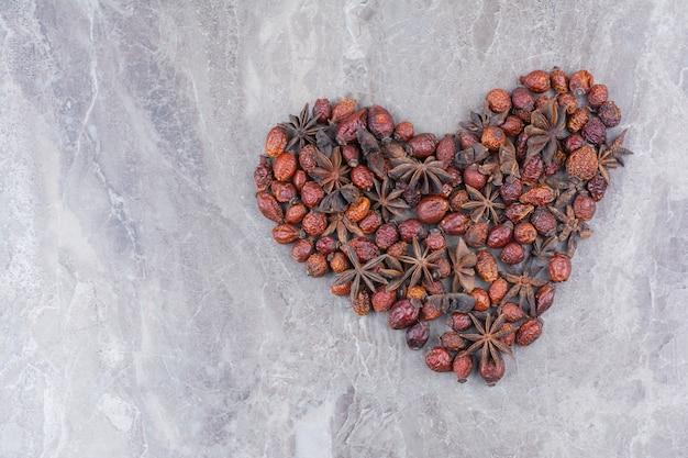 Сушеные плоды шиповника с звездчатым анисом на мраморном фоне.