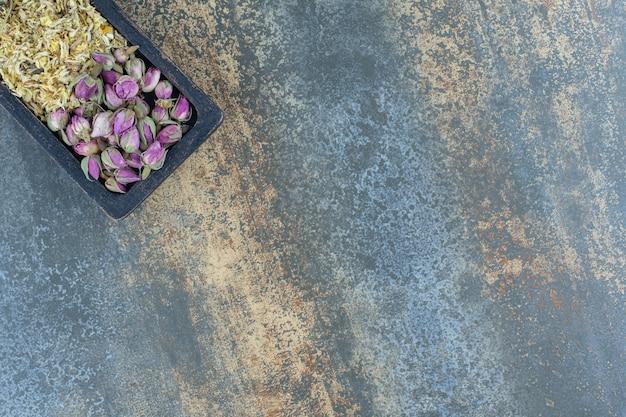黒いプレートに乾燥したバラとデイジー。