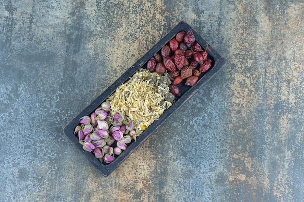 Сушеные розы, ромашки и плоды шиповника на черной тарелке.