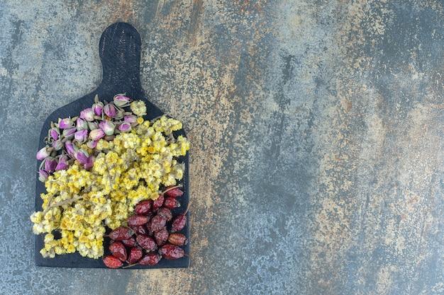 Сушеные розы, ромашки и шиповник на деревянной доске.