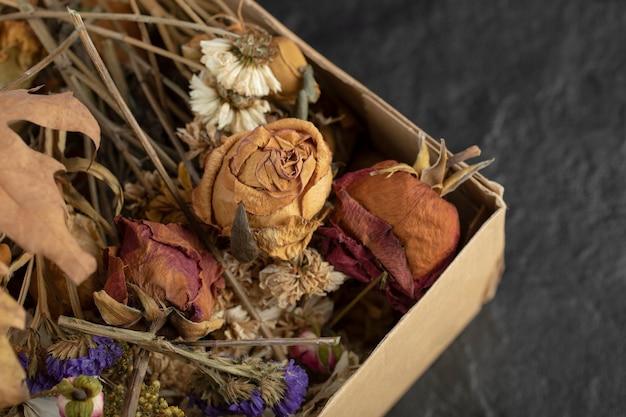 紙箱に乾燥した葉と乾燥したバラの花。