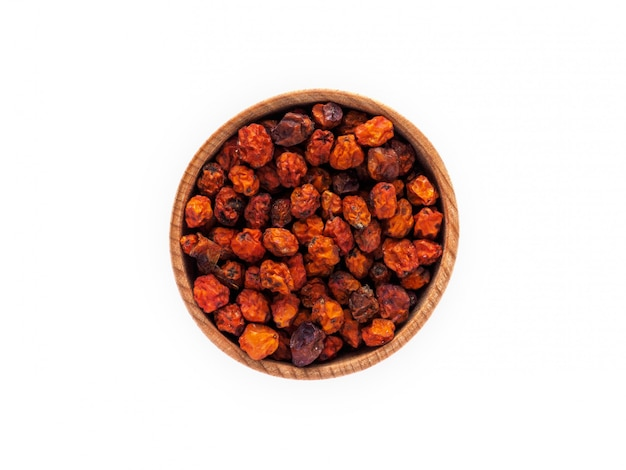Dried rowan or sorbus berries in a wooden cup on a white