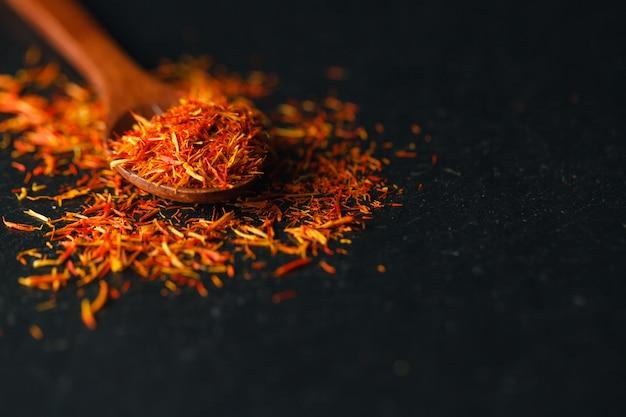 Dried saffron spice on black table. raw organic pistil powder saffron are scattered on the table. red saffron spice in a wooden spoon on black table