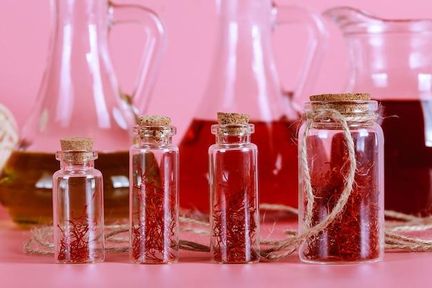 유리병에 말린 사프란 가닥과 분홍색 배경에 오일 추출물. 화장품, 의학 및 요리의 사프란.