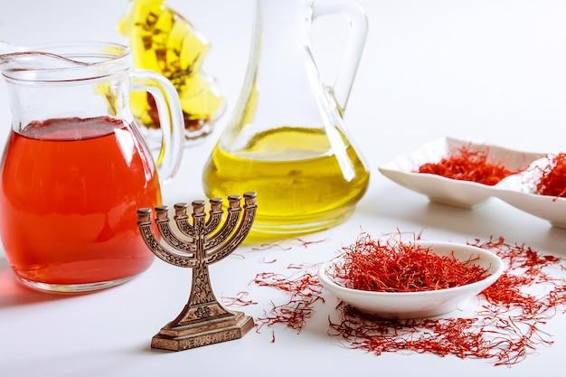유리병에 말린 사프란 실과 흰색 배경에 오일 추출물. 메노라. 이스라엘 요리의 향신료.
