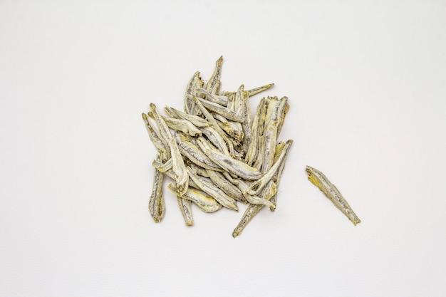 Сушеные соленые анчоусы на белом фоне