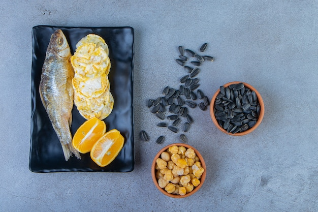 Dried salted fish, chips and sliced lemon on a platter next to bowl of chickpea and seed , on the marble surface.
