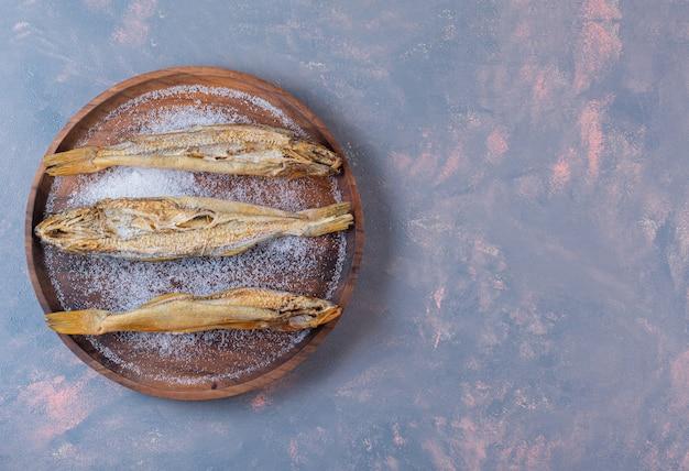 Сушеная соленая рыба на деревянной тарелке на мраморной поверхности