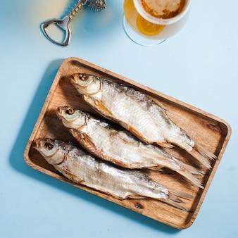 Сушеная соленая рыба на деревянном подносе.