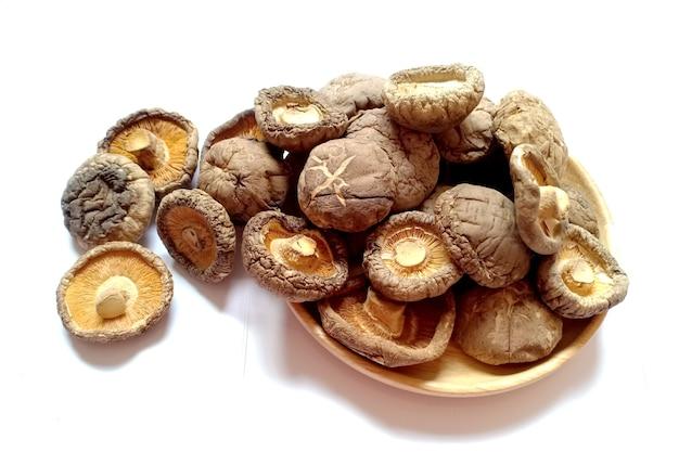 Сушеные грибы шиитаке в деревянной тарелке на белом фоне