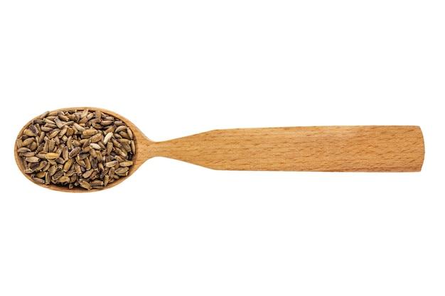 Сушеный расторопша в деревянной ложке на белом фоне.