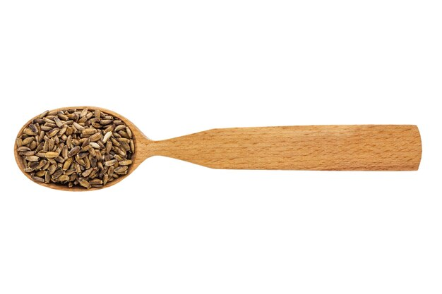 Dried silybum in a wooden spoon on a white background.