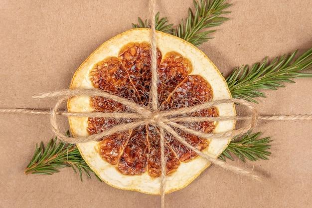 황마 밧줄로 공예 상자에 오렌지와 가문비나무 가지의 말린 조각을 닫습니다.