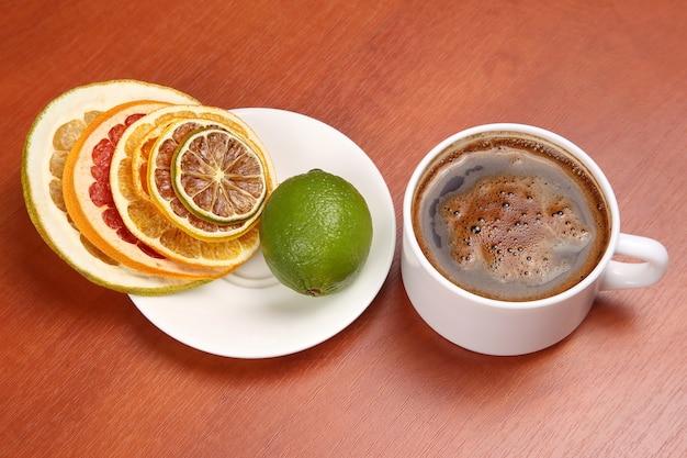 흰색 컵에 다양한 감귤류와 블랙 커피의 말린 조각