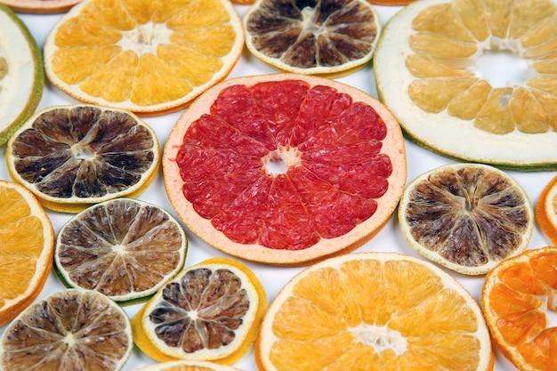 白で隔離のさまざまな柑橘系の果物のクローズアップの乾燥スライス
