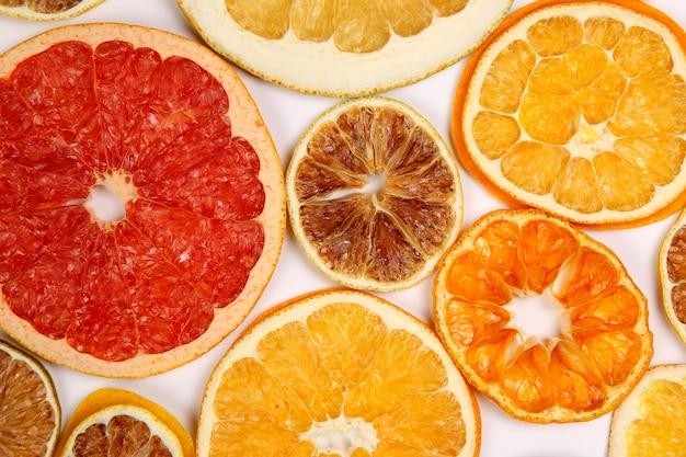 Сушеные ломтики различных цитрусовых на белом фоне