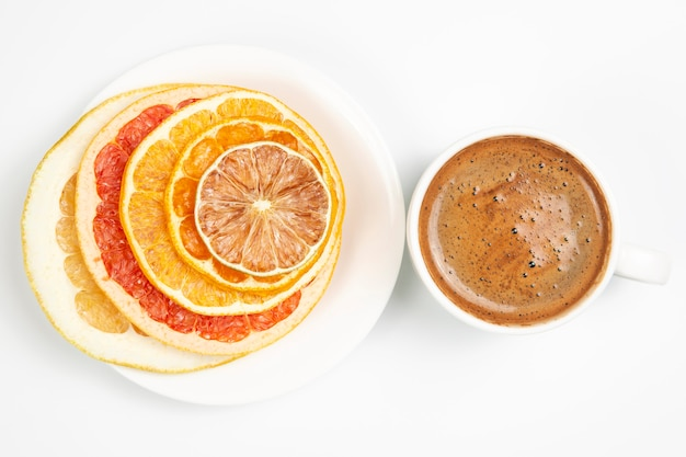 Dried slices of various citrus fruits and black coffee in a white cup