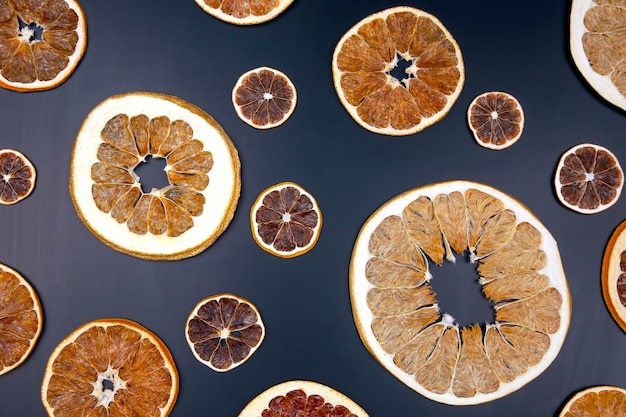 Dried slices of various citrus fruits on black wooden board, top view