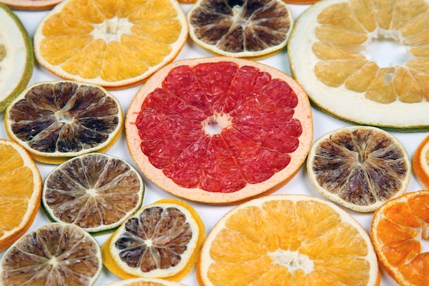 Dried slices of various citrus fruits closeup isolated on white