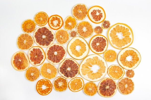 Dried slices of various citrus fruits on white