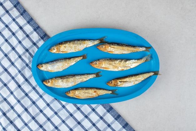 파란색 접시에 작은 생선을 말린
