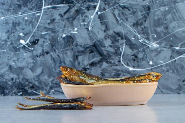 Spratto piccolo salato essiccato in una ciotola, sullo sfondo di marmo.