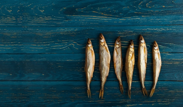 Dried smelt fish is an ideal snack for beer. it lies on a wooden background of dark blue boards.