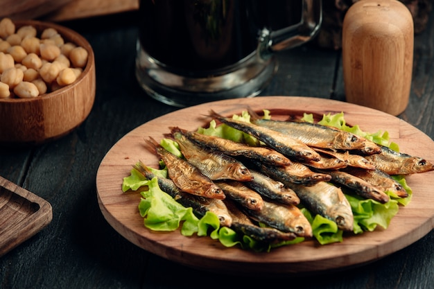 Dried smoked sprat layered on lettuce leaves served on round wood platter