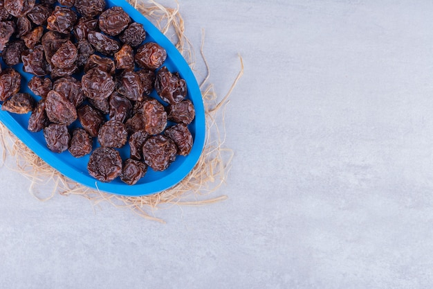 Dried sour cherry plums inside a dish isolated on concrete surface