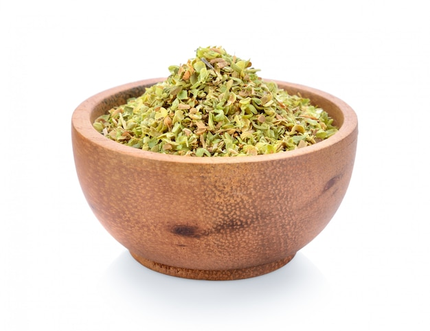 Dried spice of oregano herbs in wood bowl on white space