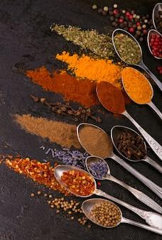 Сушеные специи - перец, куркума, перец, анис, лаванда, аджика, кинза в старых ложках на черном фоне.