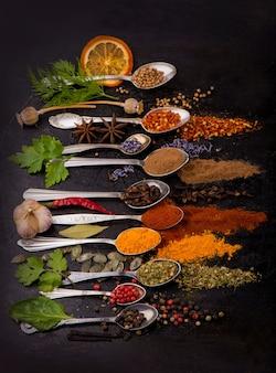 乾燥したスパイス-黒の背景に古いスプーンでコショウ、ターメリック、パプリカ、アニス、ラベンダー、アジカ、コリアンダー