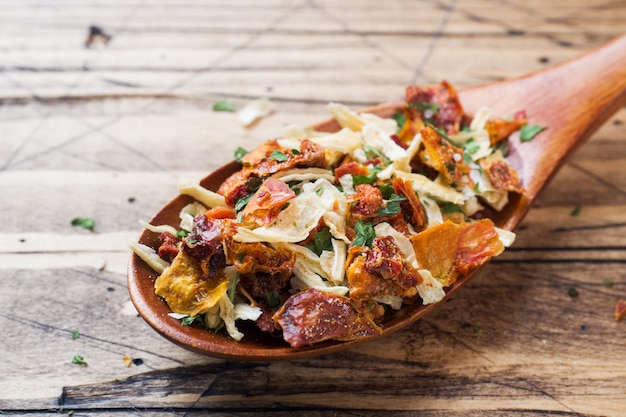 Dried spices, sun-dried tomatoes, dried carrots, basil and provencal herbs in a wooden spoon on a wooden table. copy space.