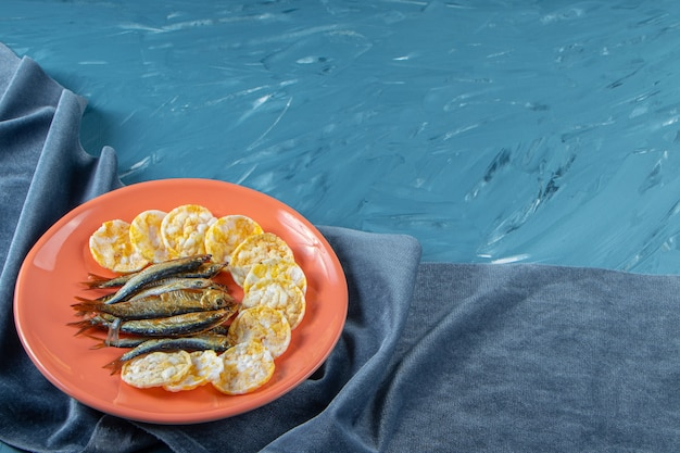 Dried sprat and cheese chips in a plate on the towel , on the blue background.