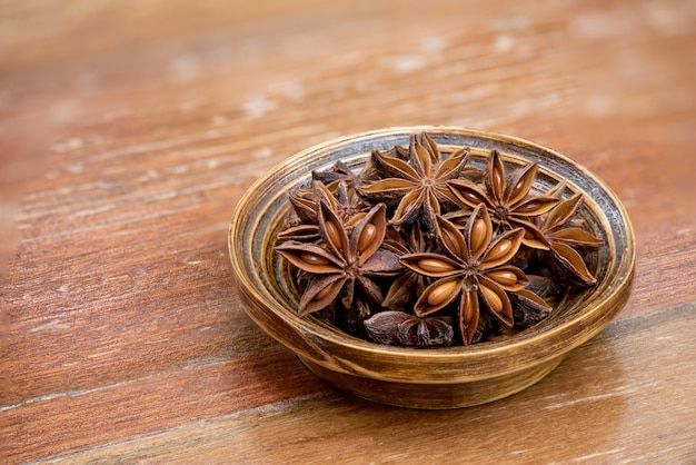 Dried star anise or illicium verum fruits on an old wood .