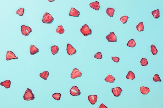 파란색 배경에 말린 딸기 조각 칩이 흩어져 있습니다. 과일 칩. 건강한 식생활 개념, 간식, 설탕 없음. 상위 뷰, 복사 공간입니다.