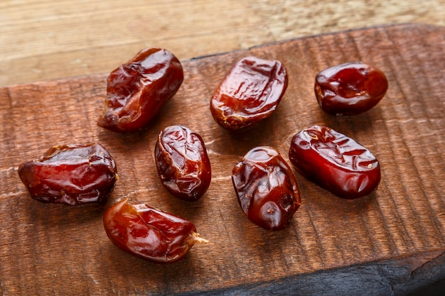 Dried sweet dates on a brown wooden board