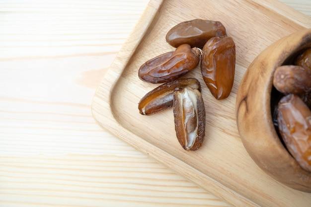 Dried of sweet dates palm fruits on wooden plate.