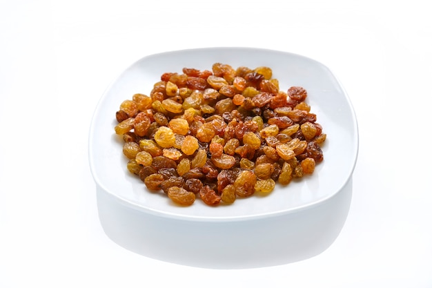 Dried sweet golden raisins in a white plate on an isolate on a white surface