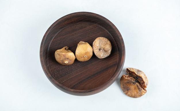 Fichi gustosi secchi sul piatto di legno.