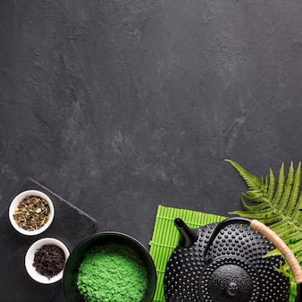 Dried tea herb and green matcha tea powder with teapot on black textured background