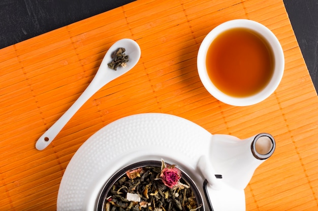 Dried tea herb and tea on place mat with ceramic teapot